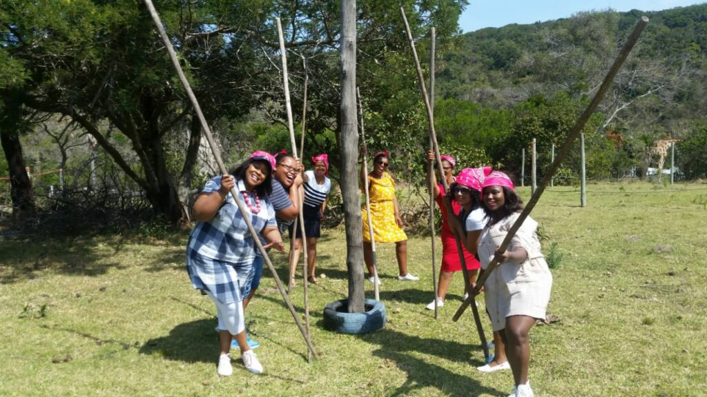 Teambuilders taking part in a teambuilding activity of lifting a tyre over a pole, using long sticks